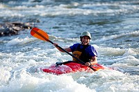 A female kayaker in a playboat paddles through rapids on the Clark Fork River, Missoula, Montana.