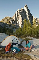 A woman camping below Prussik Peak, Enchantment Peaks, Alpine Lakes Wilderness, Leavenworth, Washington.