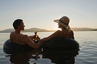 A young couple relax with a cold beverage while floating in a lake at sunset in inner tubes.