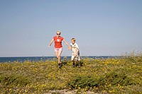 Woman and Kid Running Hand in Hand on Saaremaa Coast, Saare County, Estonia
