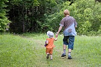 Teenage Boy with Kid Girl Hand in Hand Walking Away in Forest