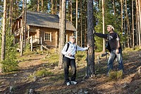 Young Hiking Couple Standing in Forest by Blockhouse in Meenikunno Landscape Reserve, Estonia