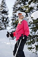 A woman skis among snow flocked trees.