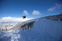 A male snowboarder spinning off a jump in Colorado.