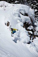 Young adult snowboarding off powder pillows in Colorado.