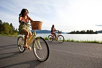 Women ride beach cruisers next to the lake in Idaho.