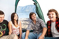Young adults camping laugh in their tent with a lake in the background in Idaho.