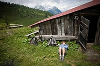 A middle aged woman takes a nap near a run down workshop, after a long hike and filling lunch in the Swiss Alps.