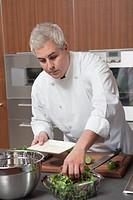 Mid_ adult chef prepares salad
