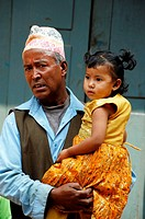 nepalis man holding his grand daughter , street life in kathmandu , nepal