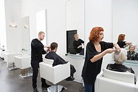 Stylists cut clients´ hair in unisex salon