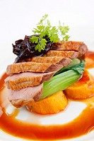 Roast duck breast on a bed of vegetables with cranberry sauce and gravy