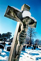Crucifix headstone in snow covered cemetery