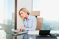 Germany, Frankfurt, Business woman using laptop in the office