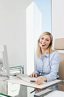 Germany, Frankfurt, Business woman wearing headset and using computer