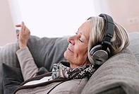 Germany, Wakendorf, Senior woman listening music
