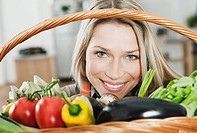 Germany, Cologne, Woman looking through vegetable basket
