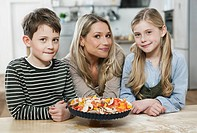 Germany, Cologne, Mother and children with pizza in kitchen