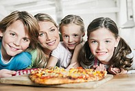 Germany, Cologne, Mother and children in kitchen, smiling, portrait