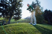 Italy, Kastelruth, Mature man playing golf on golf course