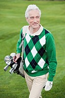 Italy, Kastelruth, Mature man walking on golf course, smiling