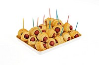 Hors d´oeuvres pigs in a blanket with toothpicks on serving tray on white background cutout.
