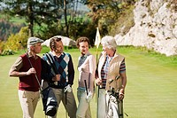 Italy, Kastelruth, Golfers on golf course, smiling