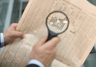 Man holding a magnifying glass over a newspaper