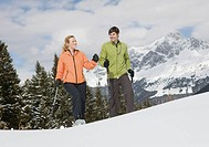 Germany, Bavaria, Young man and woman walking in a snow