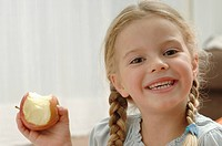 Germany, Bavaria, Girl holding apple, portrait, smiling