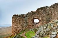 Stone wall framing a windmill, Campo de Criptana, Ciudad Real province, Castilla-La Mancha, Spain