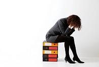 una donna mentre si copre il viso seduta su dei raccoglitori portadocumenti
