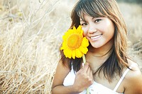 Hawaii, Oahu, Headshot of beautiful Asian woman with Sunflower.