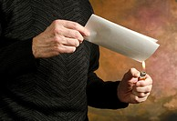 man holding butane lighter to folded document