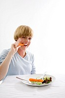 Young woman biting a carrot and eating plate of raw vegetables