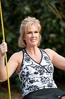 Fifty year old blond woman in fitness attire playing on a rope swing outdoors