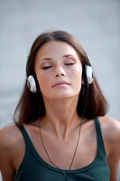 Beautiful teenage girl listening to muscic and relaxing