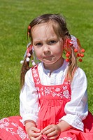 4 years old girl in red dress sitting on the grass