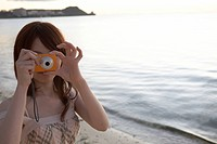 Young woman taking picture at beach, Guam, USA