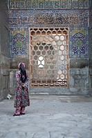 Uzbekistan, Samarkand, Sher_Dor Madrasah in the Registan square, woman standing in front