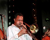 Musician playing trombone live in night club  He is Puerto Rican  For release number 24