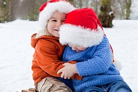 Two boys hugging in Christmas hats