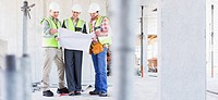 Construction workers looking at blueprints on construction site (thumbnail)