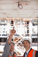 Construction workers looking at ceiling on construction site