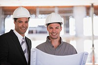 Construction worker and businessman looking at blueprints on construction site