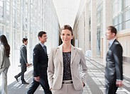 Busy co_workers waking past businesswoman