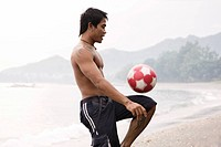 Guy playing football on beach