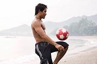 Guy playing football on beach