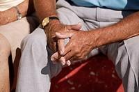 elderly man sitting with folded hands