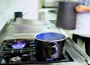 chef putting cooking pots on a gas stove